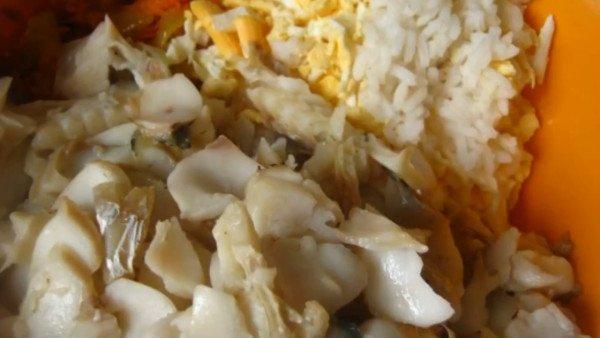 В ёмкость для приготовления салата выложить свареный тёплый рис, пассерованные овощи, рыбу