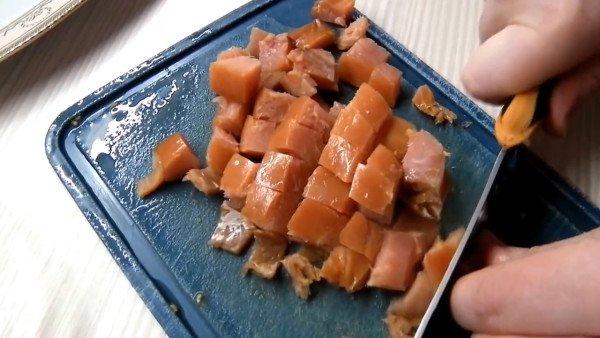 Копченую рыбу нарезать на кубики среднего размера.